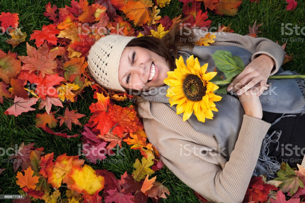 Smiling woman holding sunflower stock photo