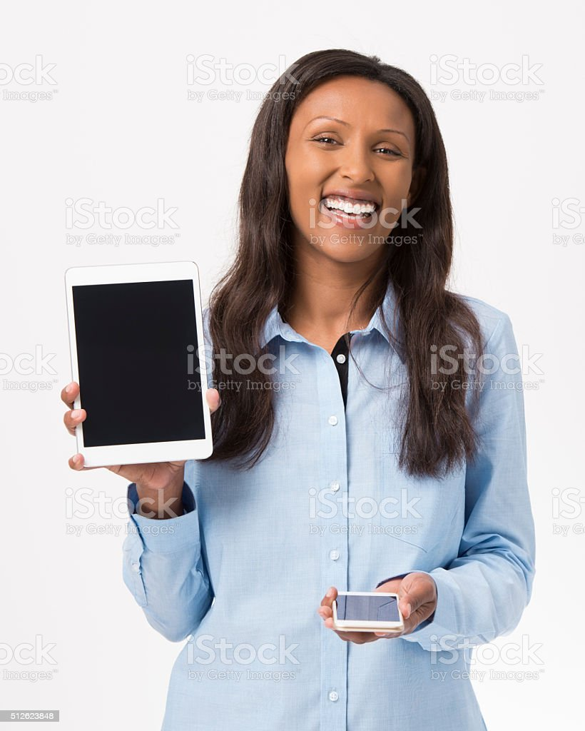 Smiling woman holding tablet and cellphone. stock photo