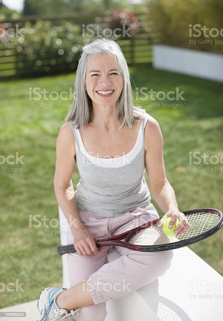 Smiling woman holding tennis racket royalty-free stock photo