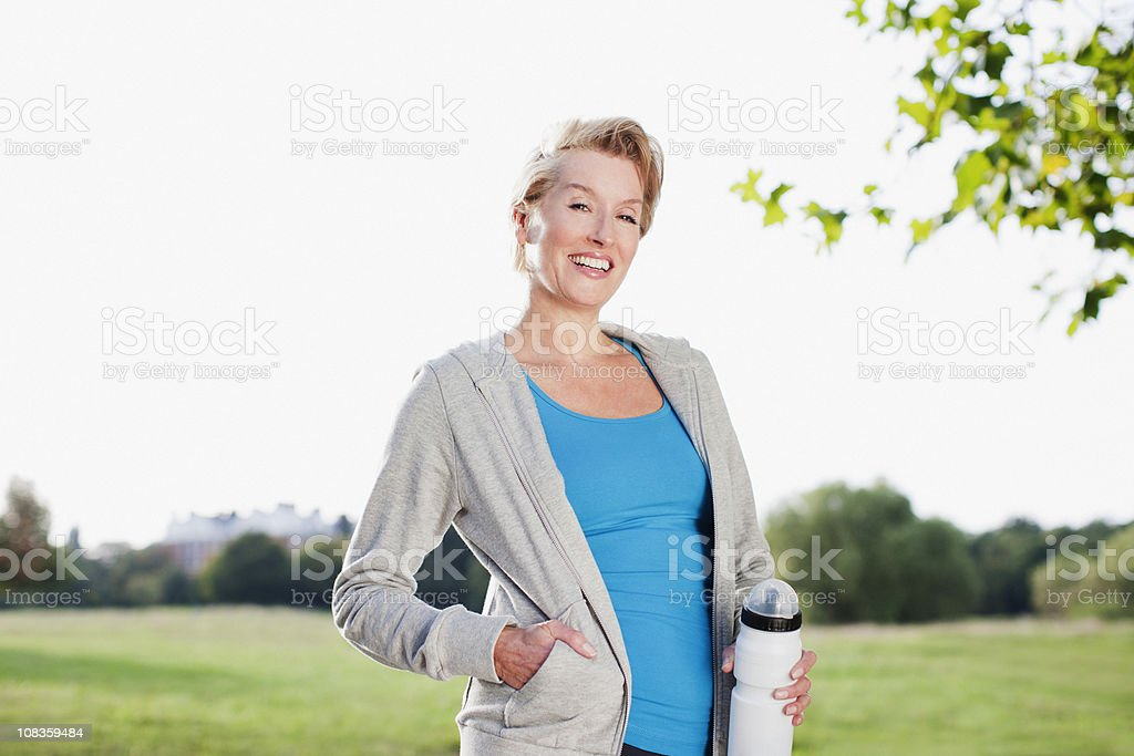 Smiling woman holding water bottle outdoors royalty-free stock photo
