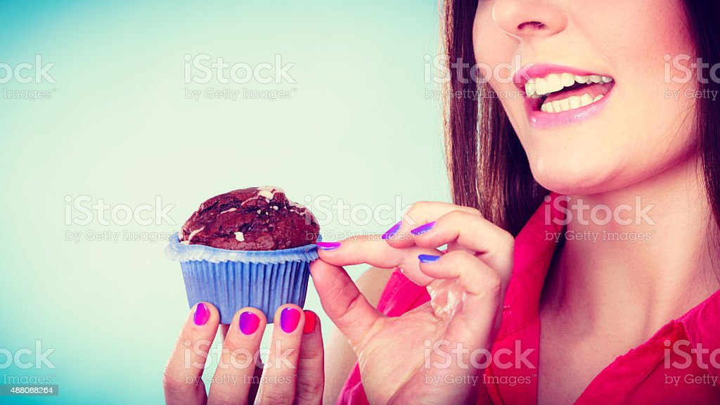 Smiling woman holds chocolate cake in hand stock photo