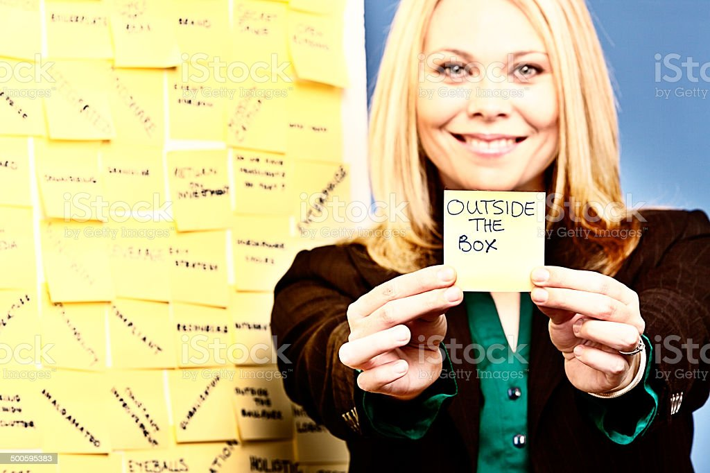 Smiling woman holds out adhesive note labelled 'Outside the Box' royalty-free stock photo