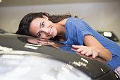 Smiling woman hugging a black car