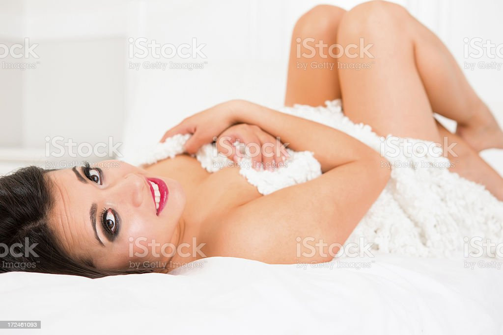 Smiling woman hugging blanket laying on bed royalty-free stock photo