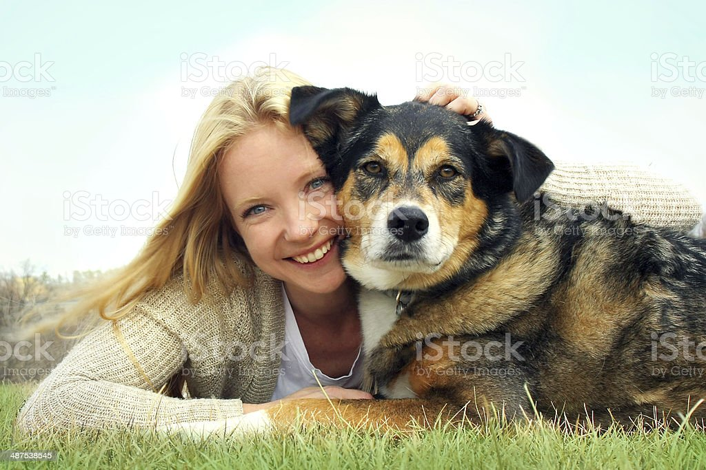 Smiling Woman Hugging German Shepherd Dog stock photo