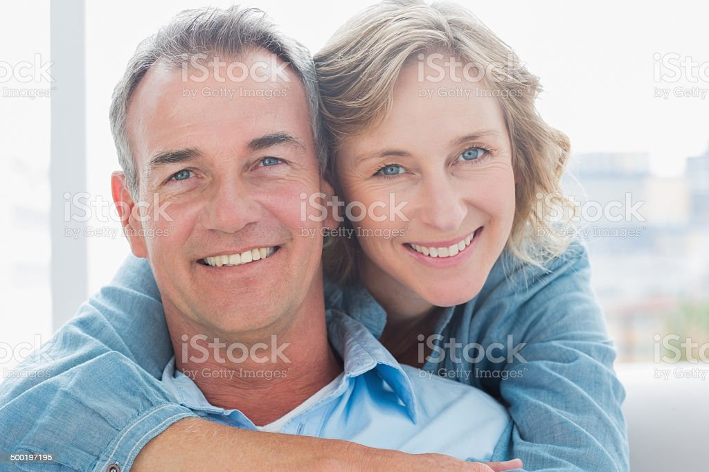 Smiling woman hugging her husband on the couch from behind stock photo