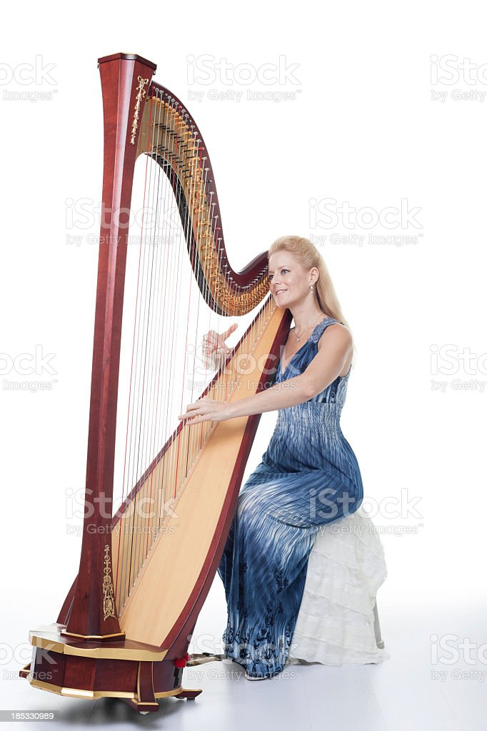 Smiling woman in a blue dress playing the harp stock photo