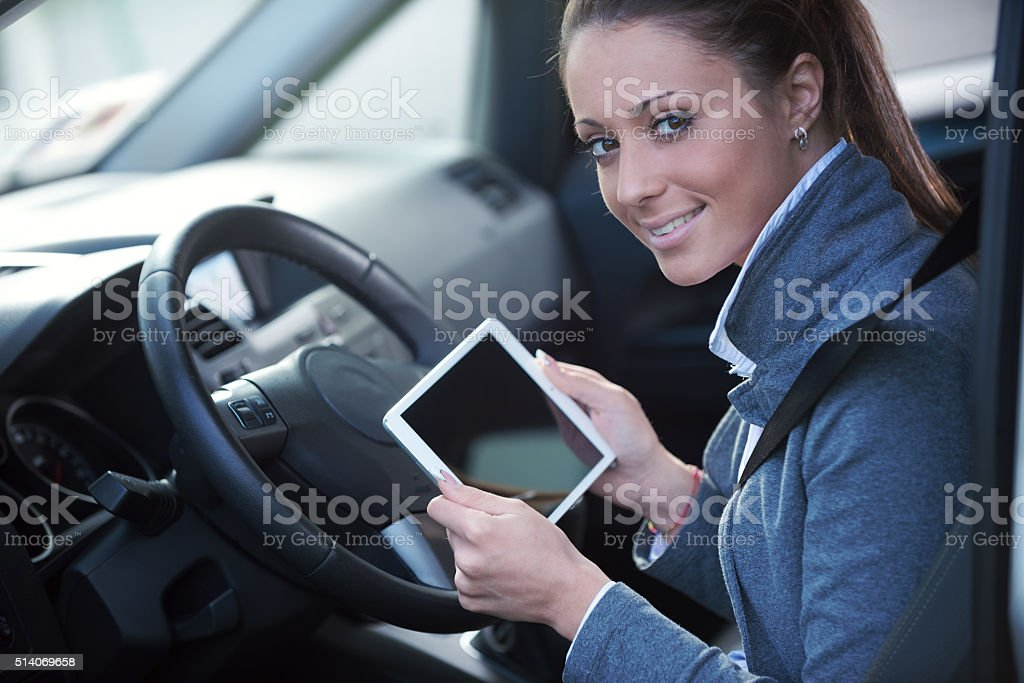 Smiling woman in a car with tablet stock photo