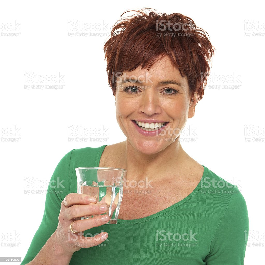 Smiling woman in a green shirt holds a glass of water. royalty-free stock photo