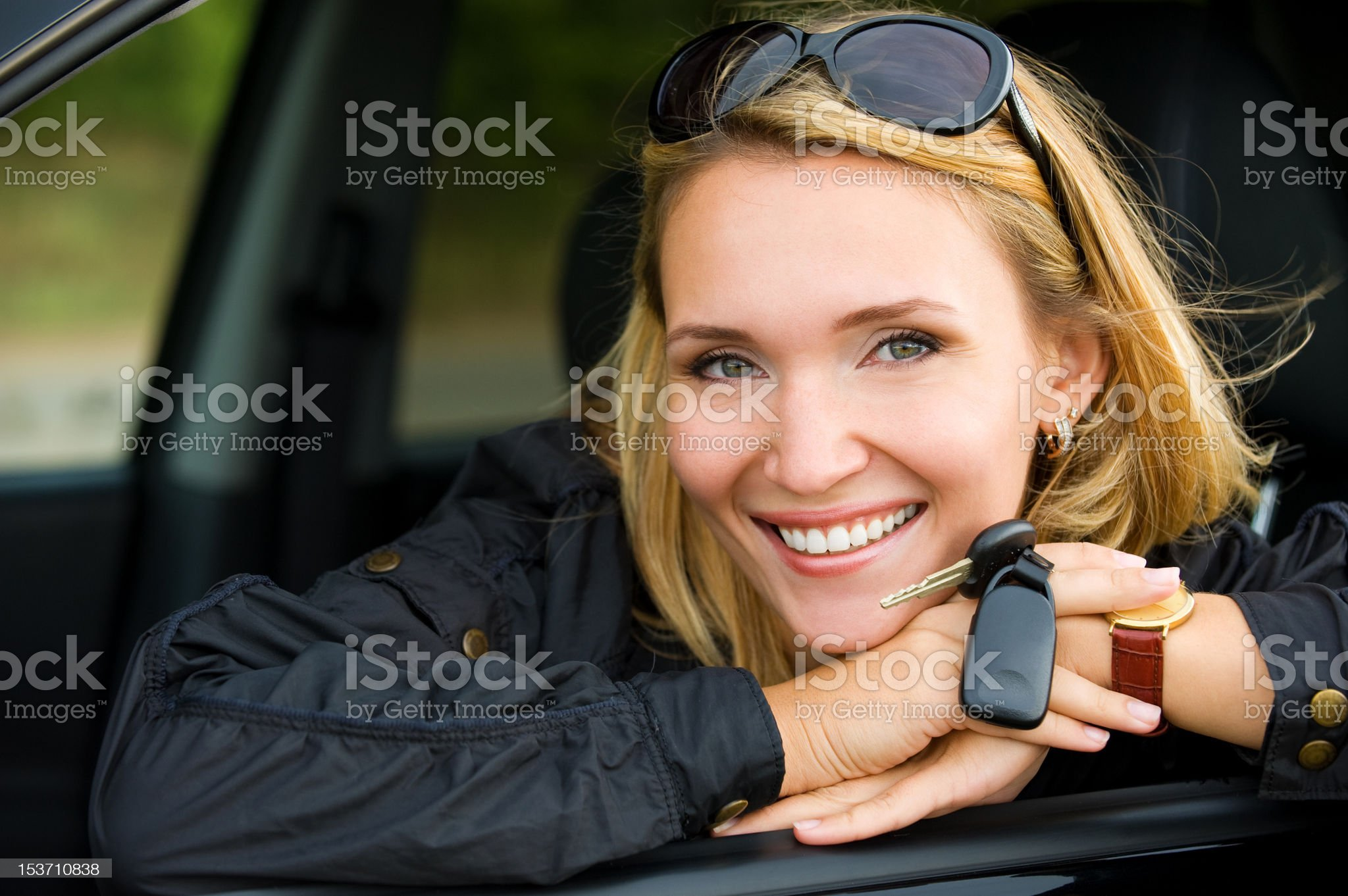 smiling woman in car with keys royalty-free stock photo