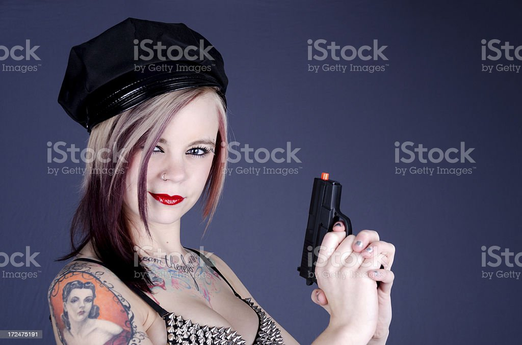 Smiling woman in fake cop hat and gun. stock photo