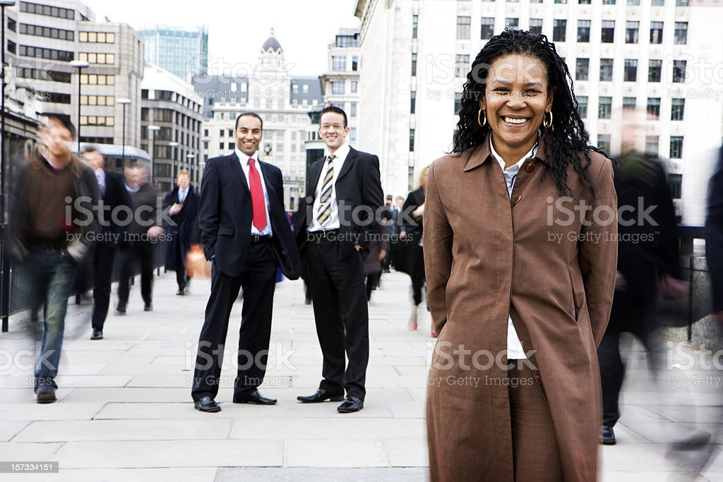 A smiling woman in front of a lot of men all facing camera. royalty-free stock photo