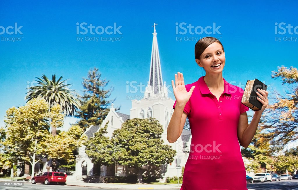 Smiling woman in front of church and waving hand stock photo