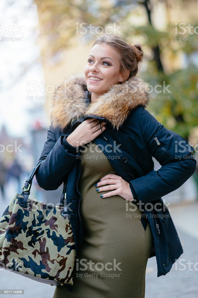 Smiling woman in green dress, camouflage purse and jacket stock photo