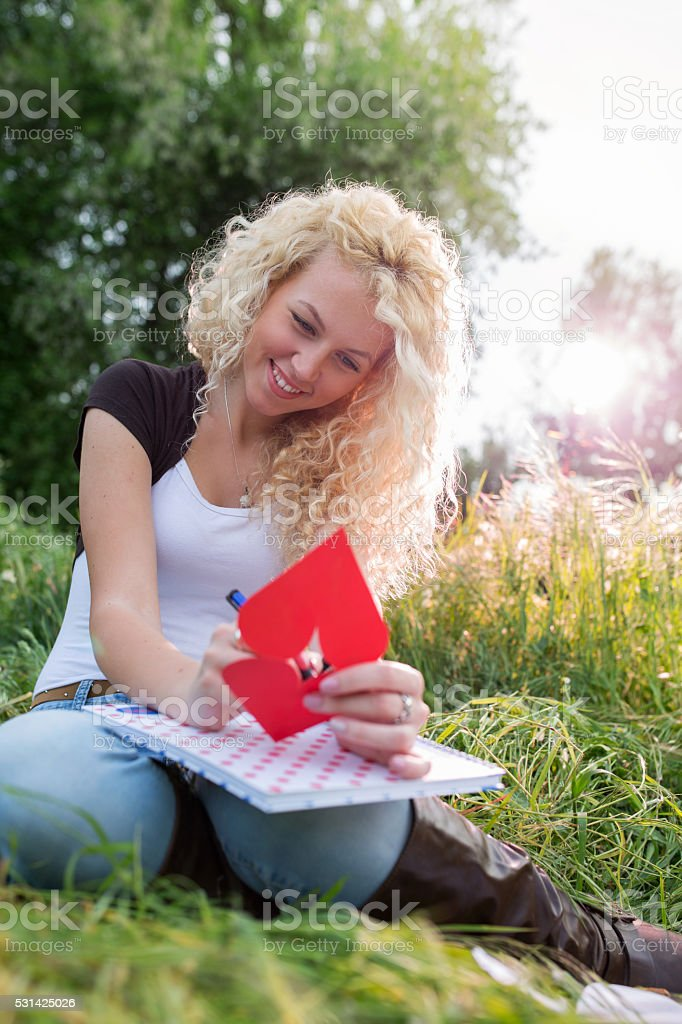 Smiling woman in nature writing message on heart shaped paper. stock photo