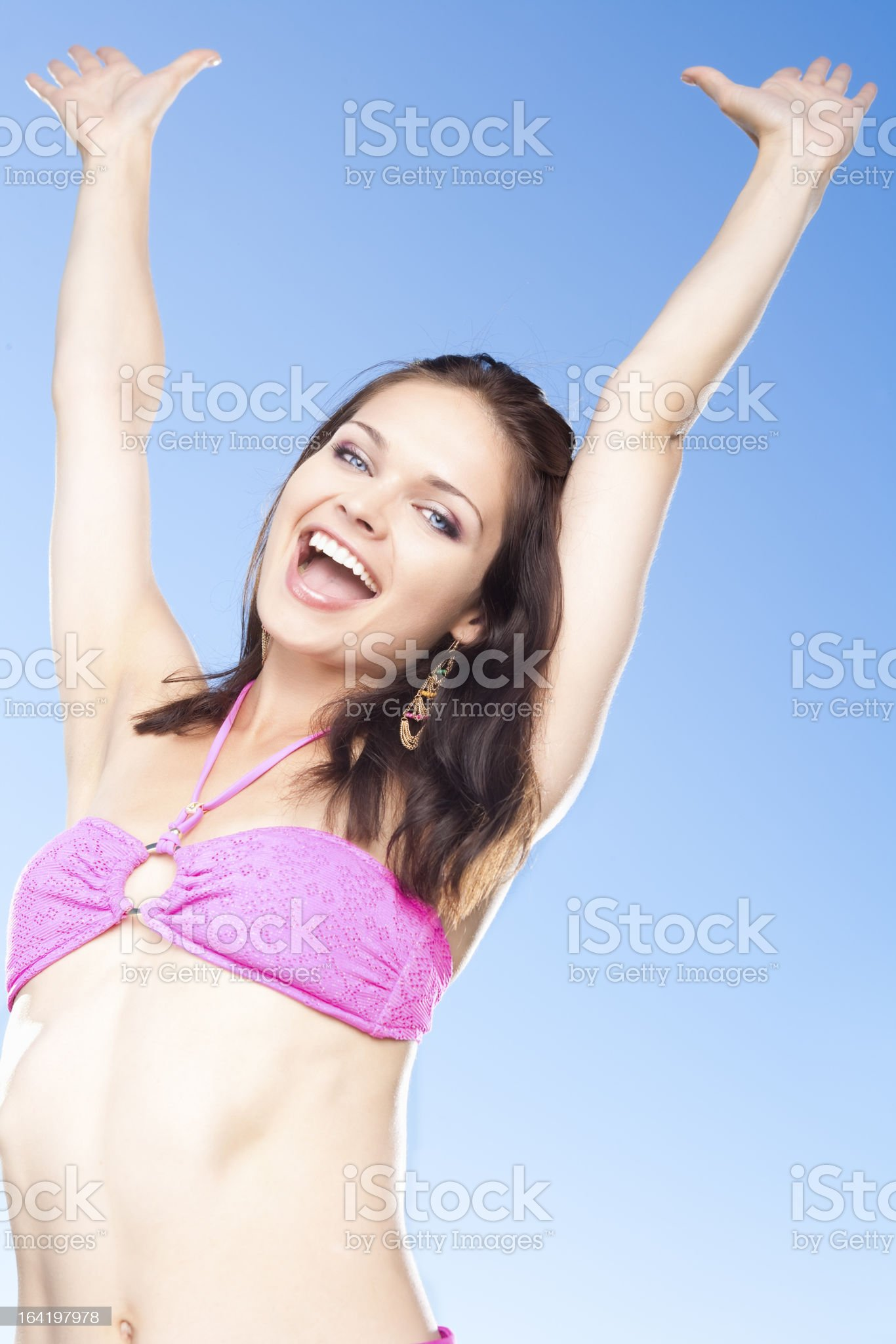 Smiling woman in pink bikini with arms raised royalty-free stock photo