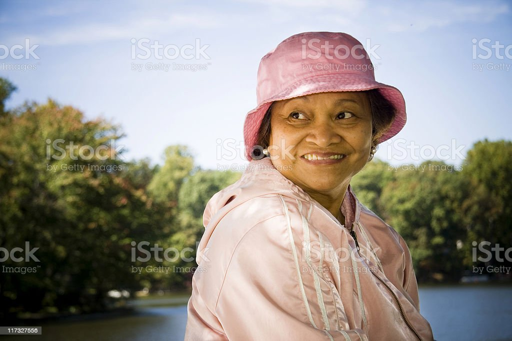 Smiling woman in pink on water indicating retirement royalty-free stock photo