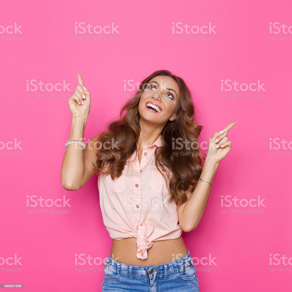 Smiling Woman In Pink Tied Shirt Pointing Up stock photo