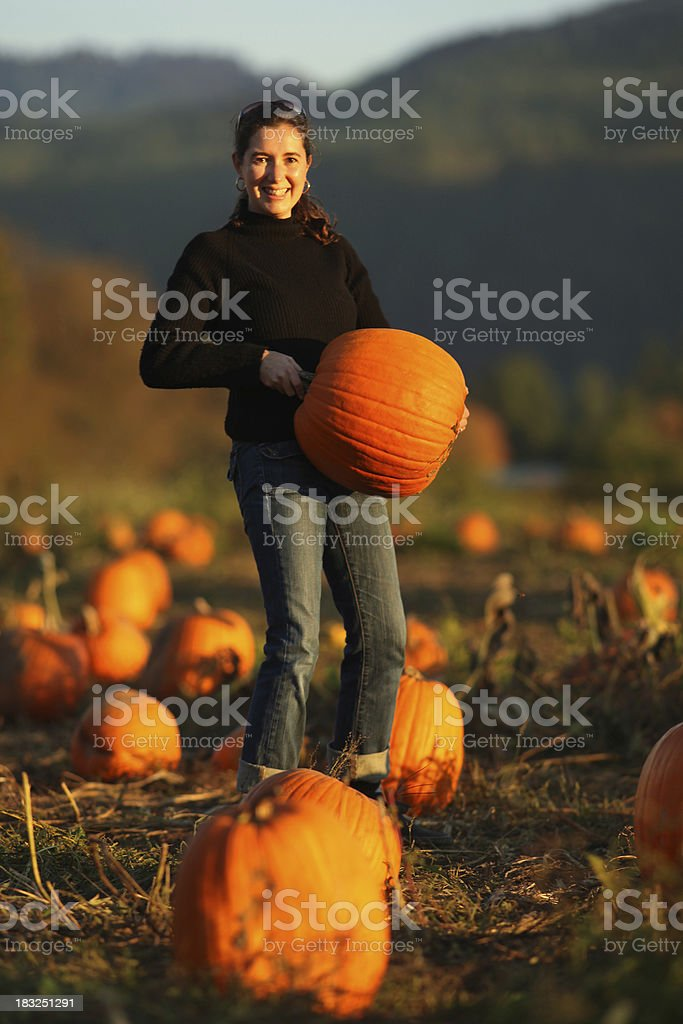 Smiling Woman in Pumpkin Patch royalty-free stock photo