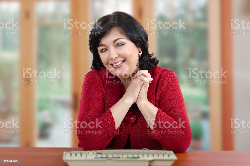 Smiling woman in red knitted jacket at the desk stock photo