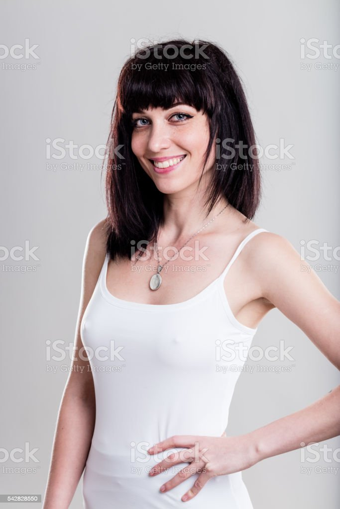 Smiling woman in tight white shirt (visible nipples version) stock photo