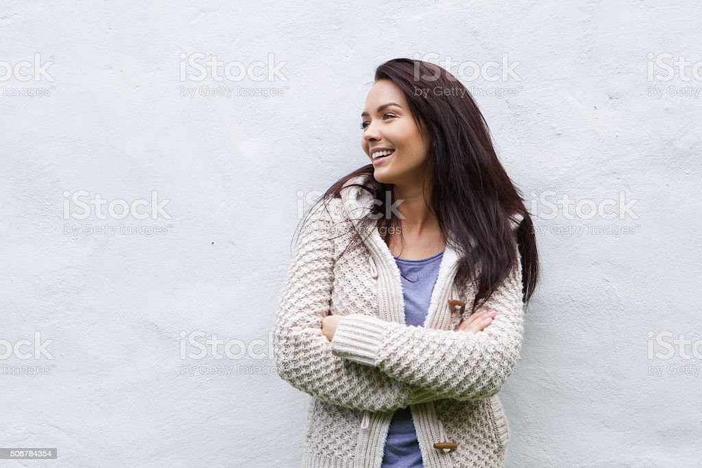 Smiling woman in wool sweater standing against white wall stock photo