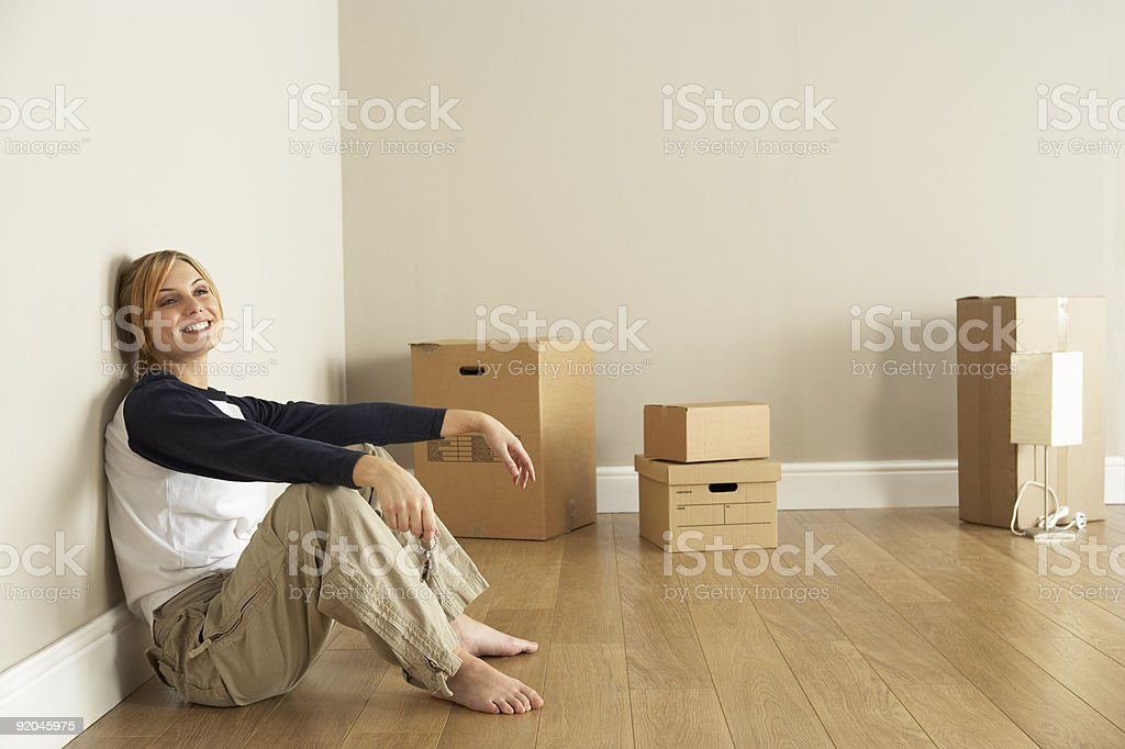 Smiling woman inside new home surrounded by moving boxes royalty-free stock photo