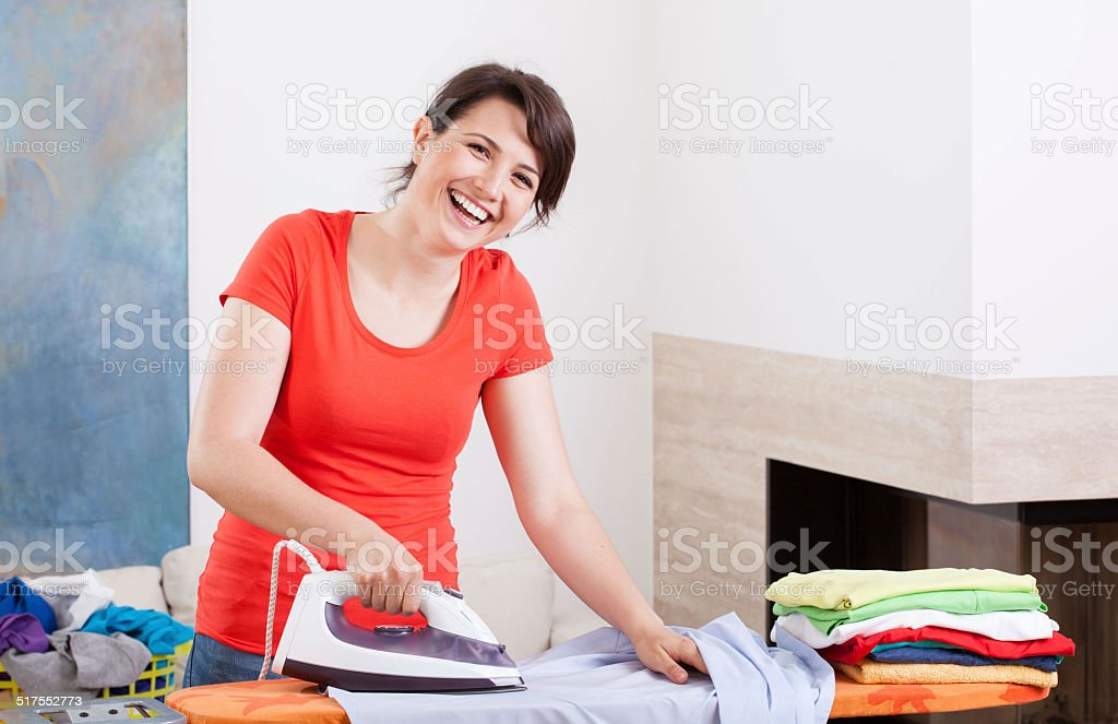 Smiling woman ironing clothes stock photo