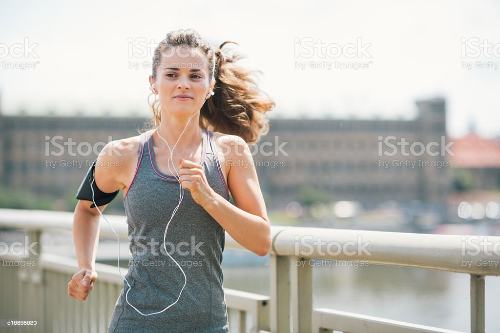 Smiling woman jogging in urban setting listening to music stock photo