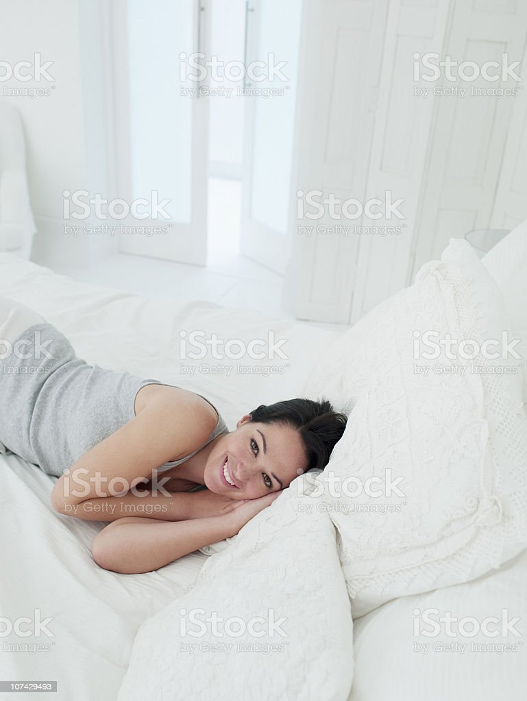 Smiling woman laying in bed royalty-free stock photo