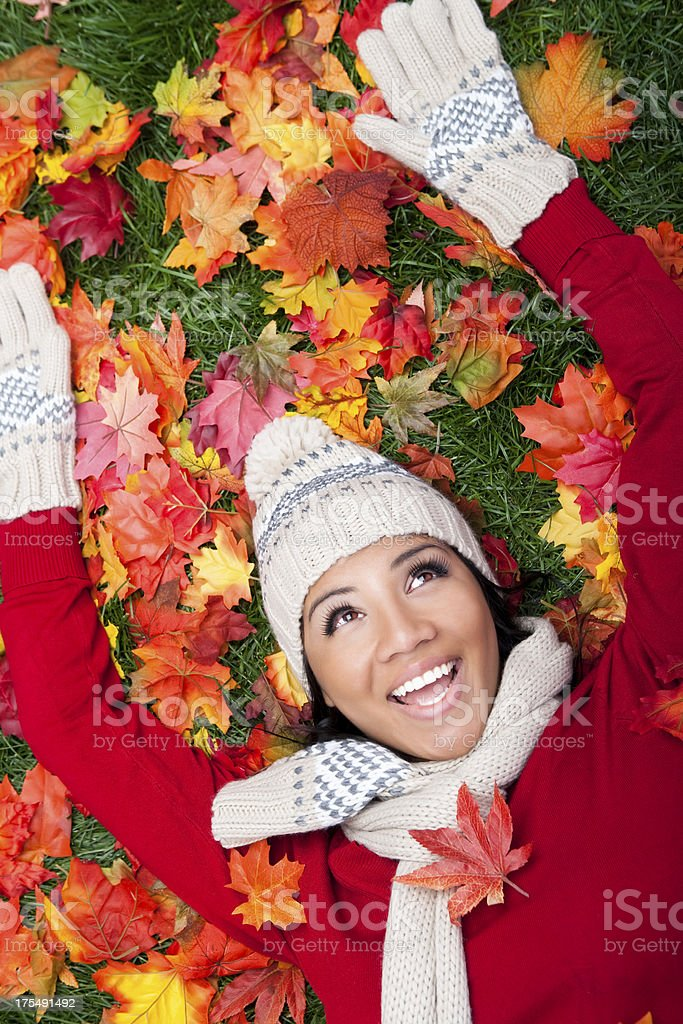 Smiling woman laying on autumn leaves royalty-free stock photo