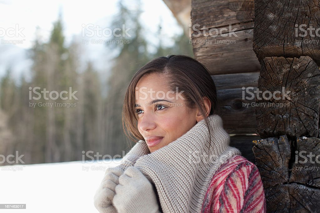 Smiling woman leaning against cabin wall in snow royalty-free stock photo