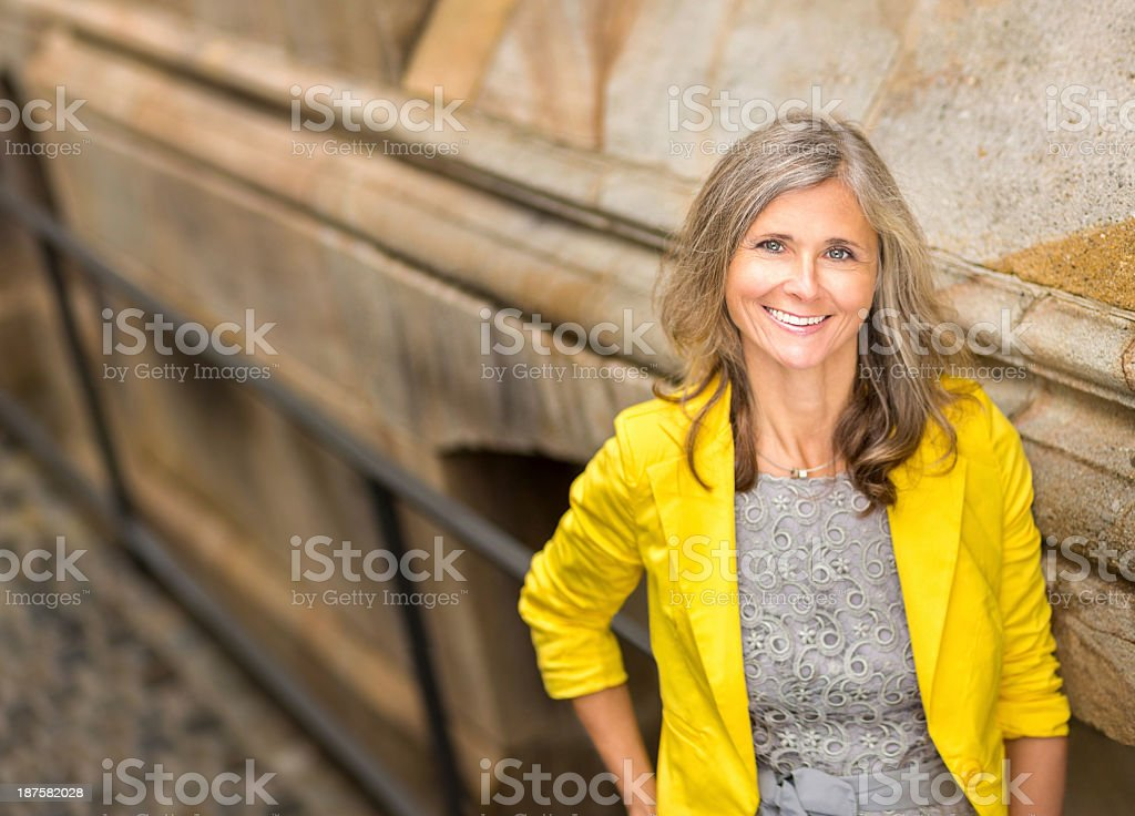Smiling Woman Leaning Against Wall stock photo