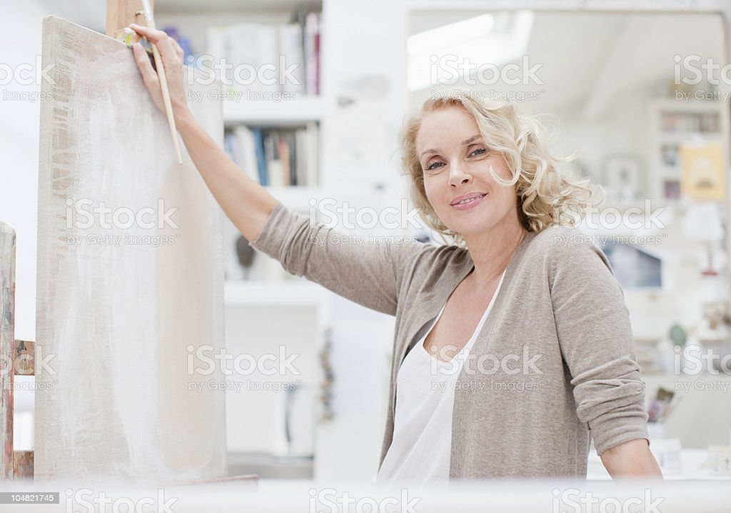 Smiling woman leaning on canvas in art studio royalty-free stock photo