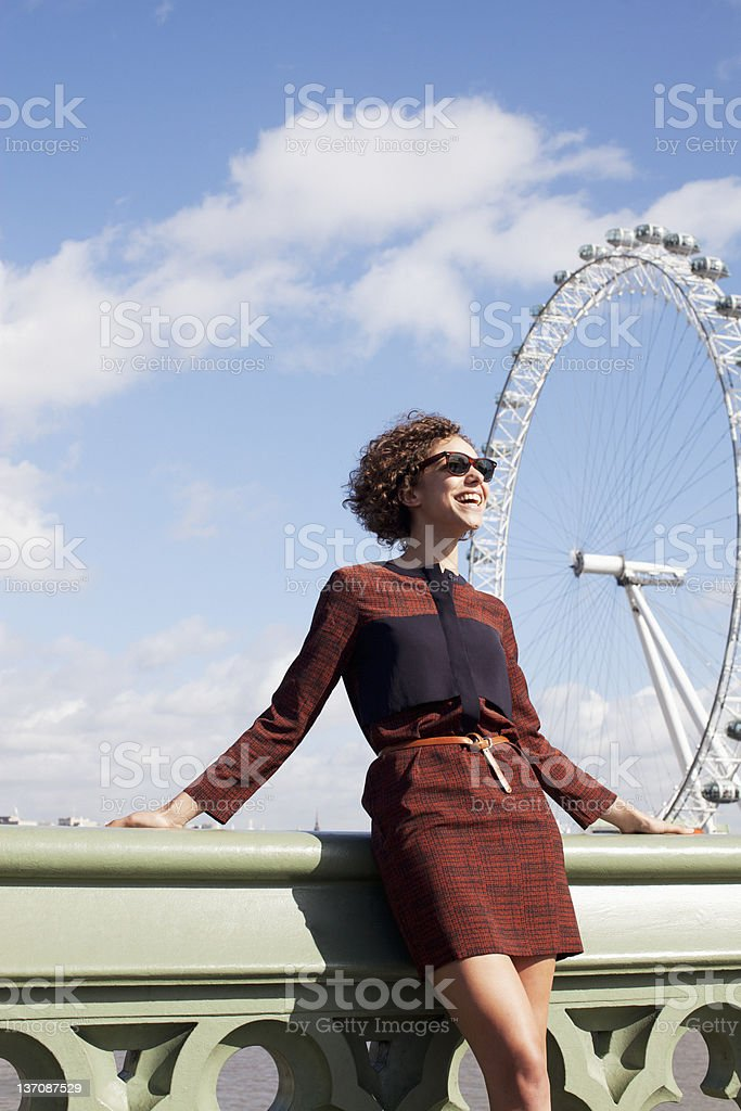 Smiling woman leaning on railing of bridge in front of ferris wheel royalty-free stock photo