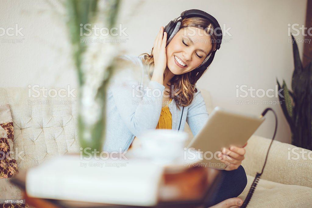 Smiling woman listening to music at home stock photo
