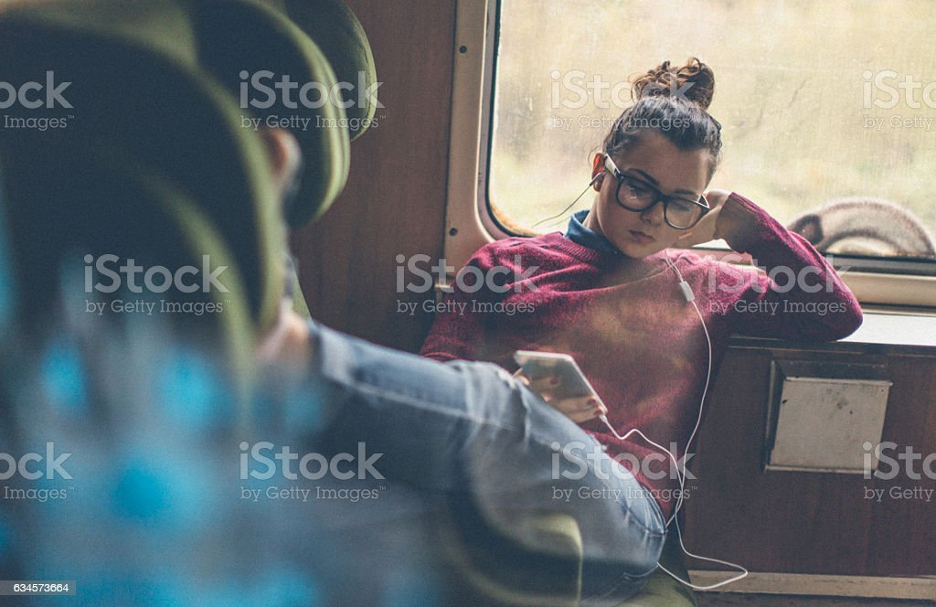 Smiling woman listening to music on smart phone in subway stock photo