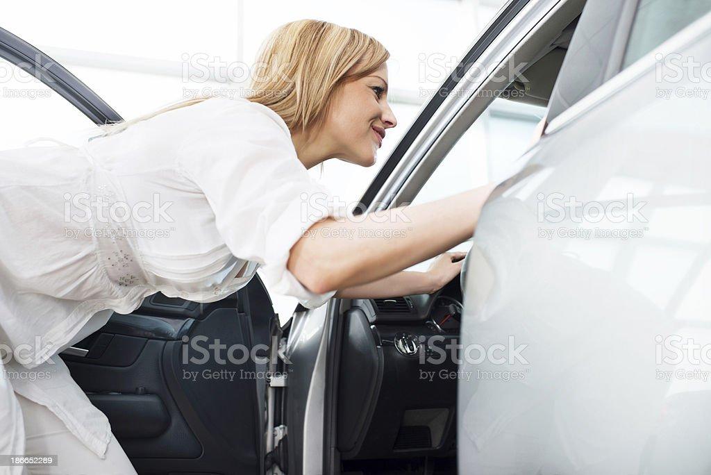 Smiling woman looking at car interior. royalty-free stock photo