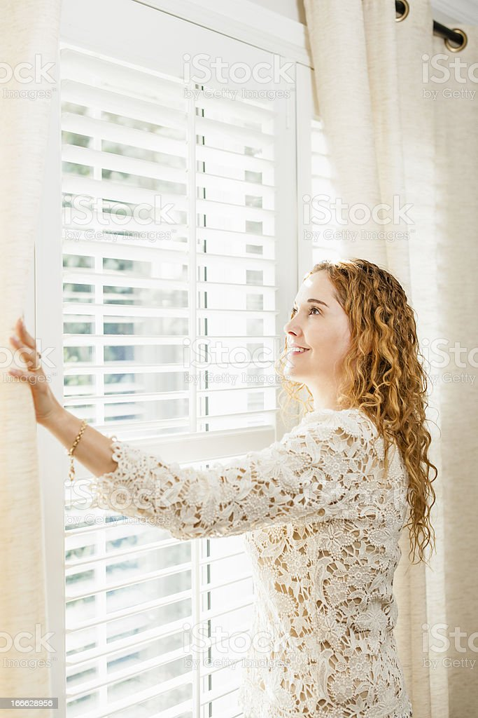 Smiling woman looking out window royalty-free stock photo