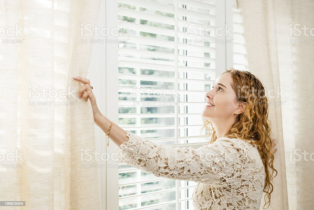 Smiling woman looking out window stock photo