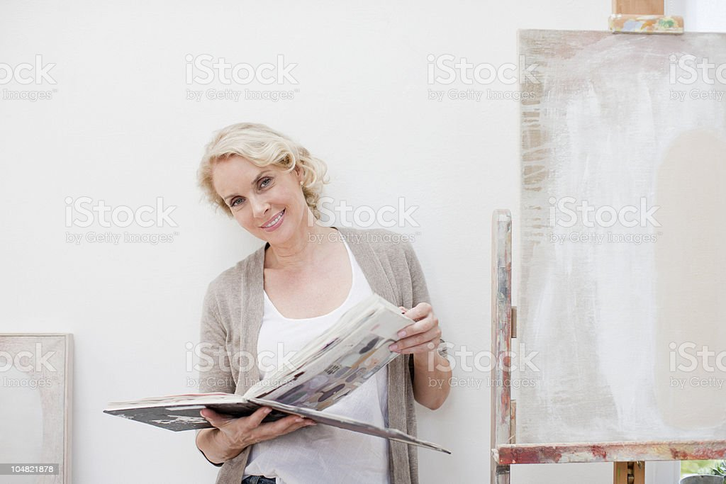 Smiling woman looking through book next to canvas in art studio royalty-free stock photo