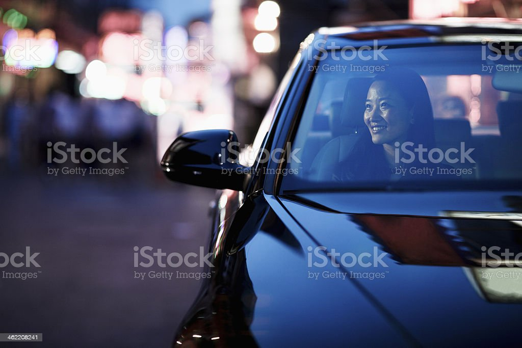 Smiling woman looking through car window at the city nightlife stock photo