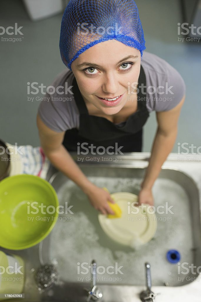 Smiling woman looking up from washing dishes royalty-free stock photo
