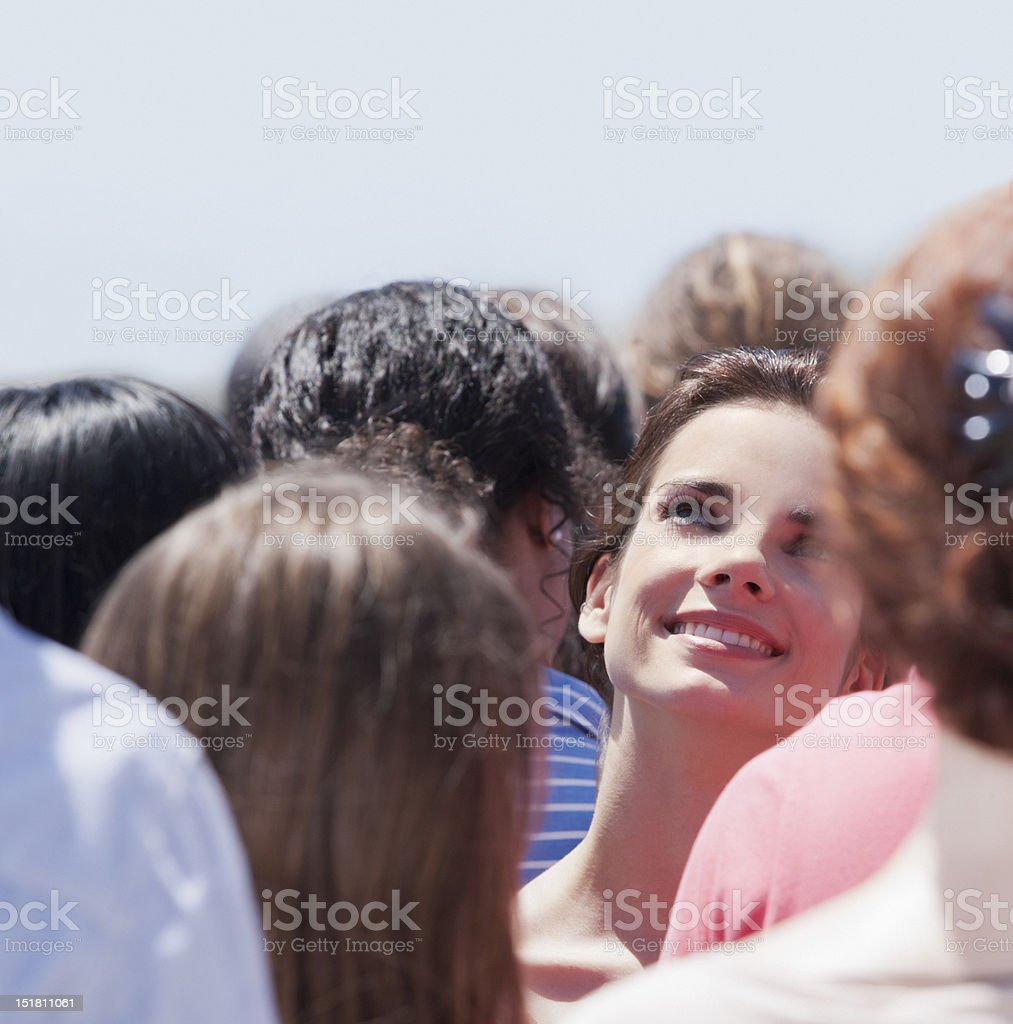 Smiling woman looking up in crowd stock photo