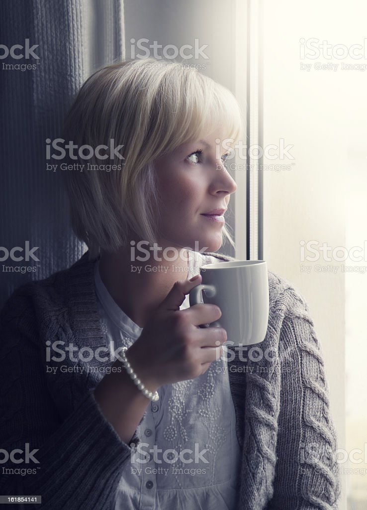 Smiling woman looks out of the window royalty-free stock photo