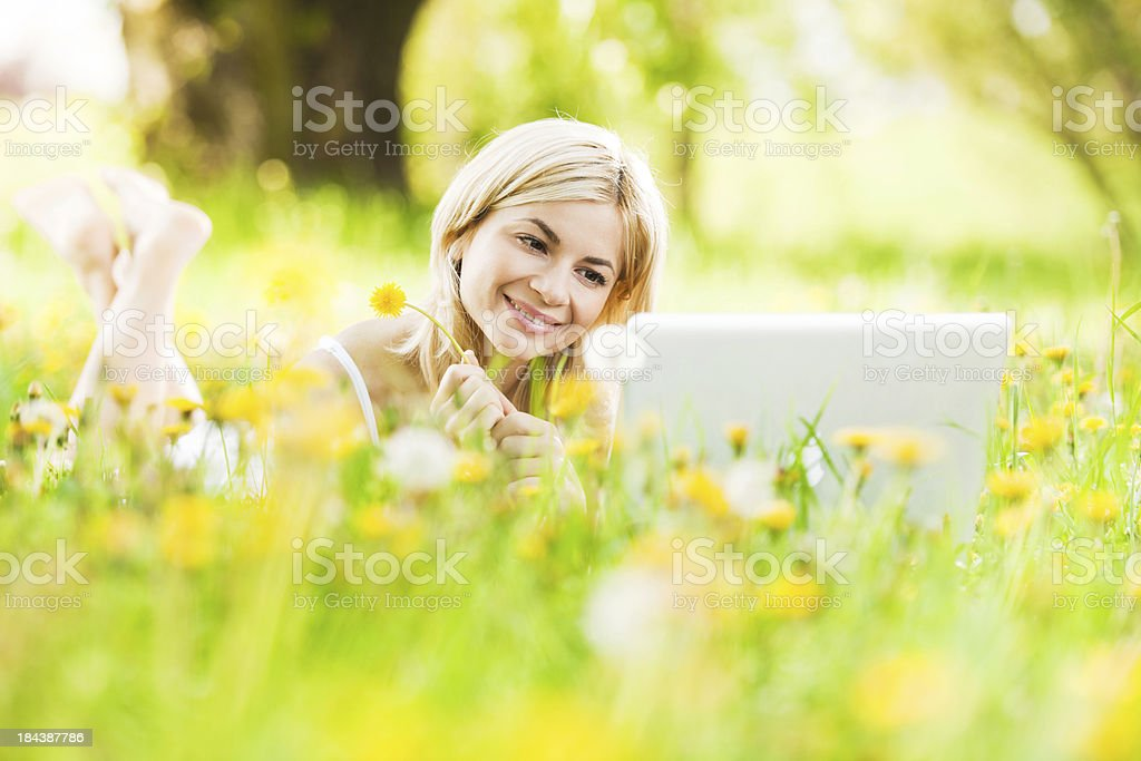 Smiling woman lying and using her laptop in the nature. royalty-free stock photo