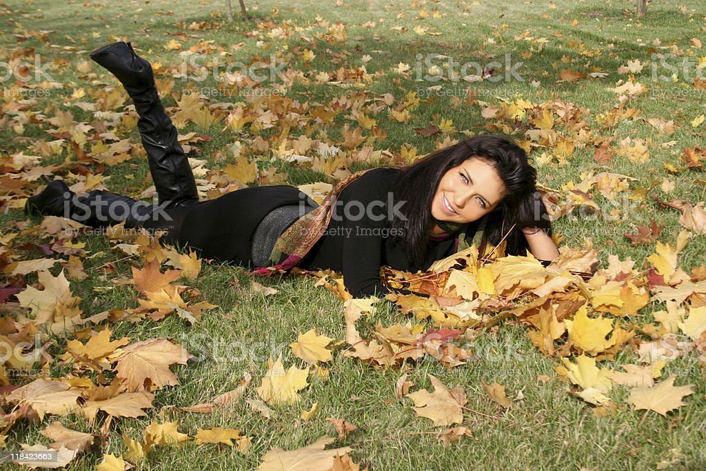 Smiling woman lying on a carpet of leaves royalty-free stock photo