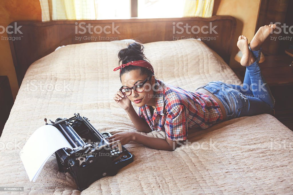 Smiling woman lying on bed legs crossed stock photo