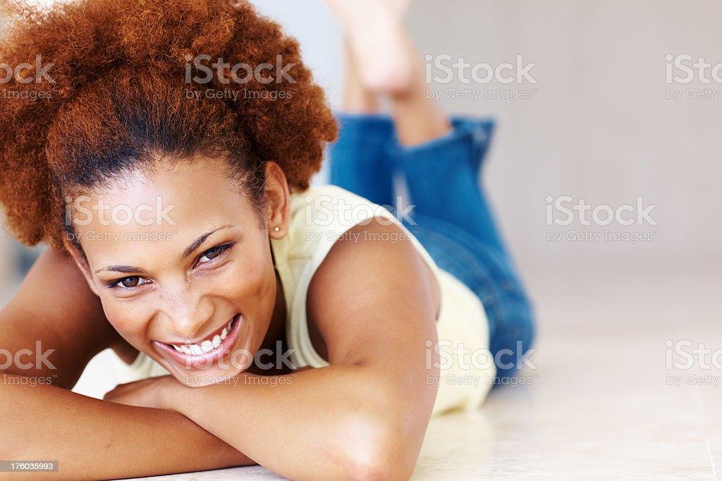 Smiling woman lying on floor stock photo