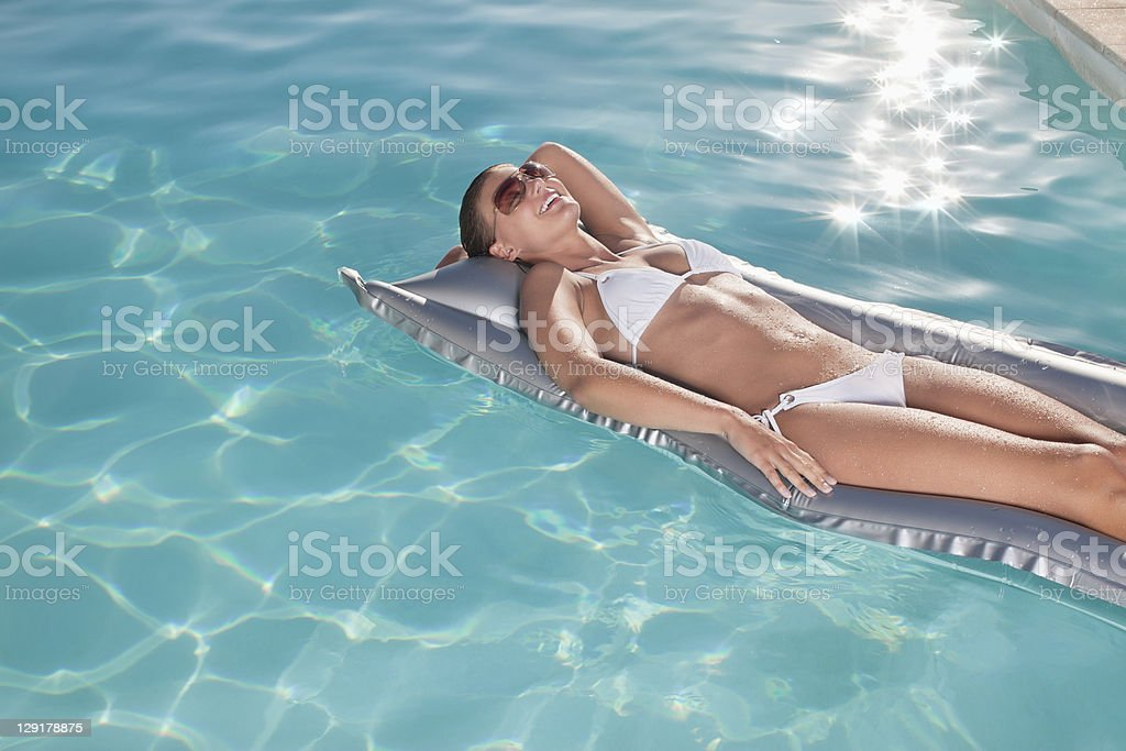 Smiling woman lying on pool raft royalty-free stock photo